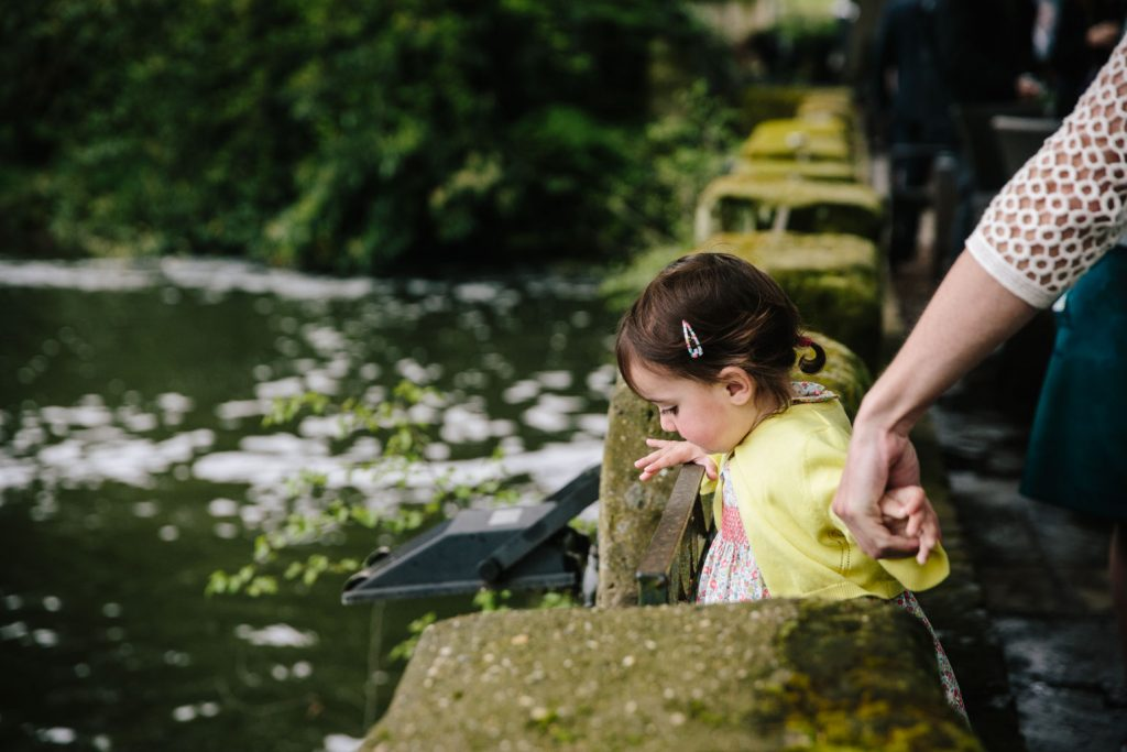 Little girl looking down at the river at the Saxon Mill, Warwickshire