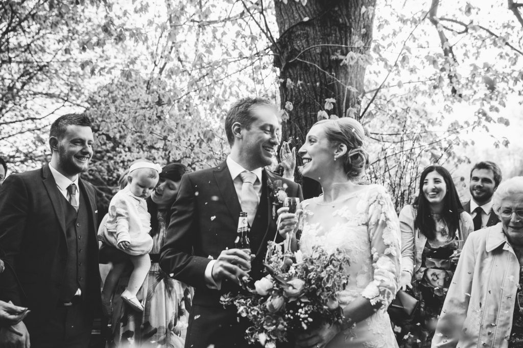 Black & white image of confetti, bride and groom, Saxon Mill wedding