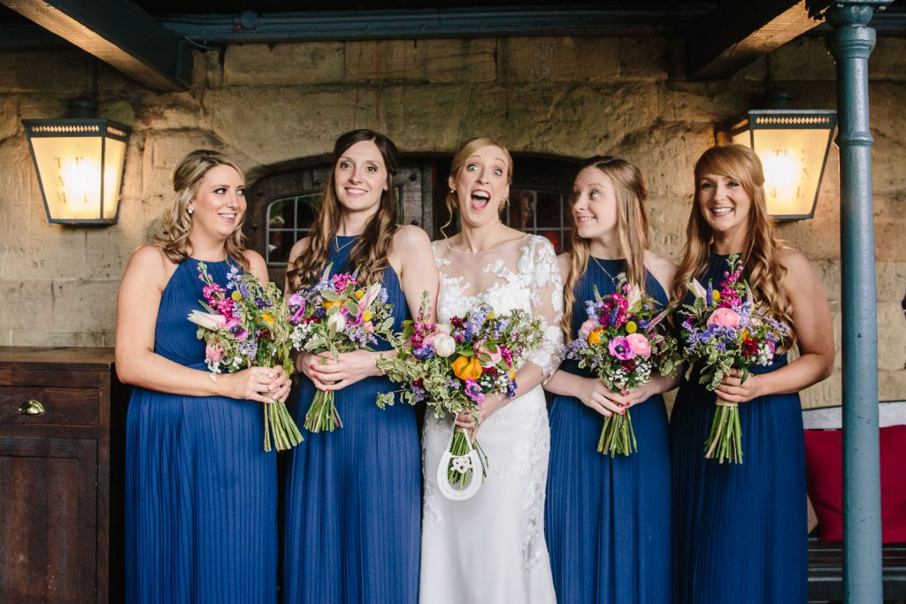 Group shot of Bride & Bridesmaids, laughing. Saxon Mill wedding