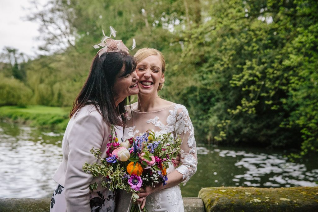 Mum kissing daughter, bride at wedding