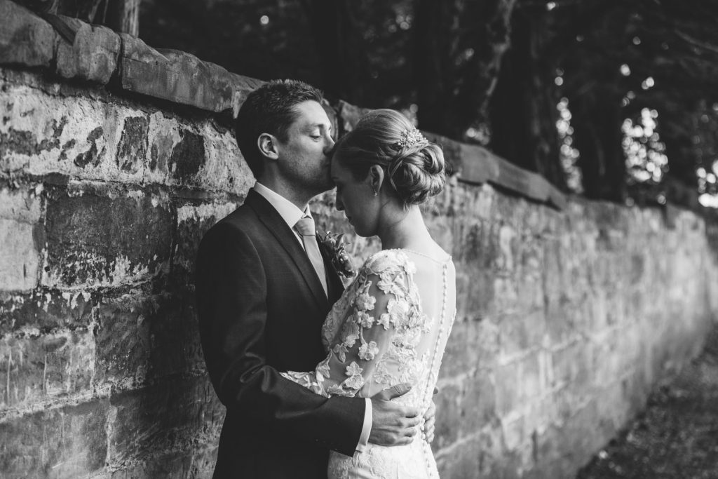 Groom kissing bride's forehead, back and white image, sAxon Mill, Warwickshire