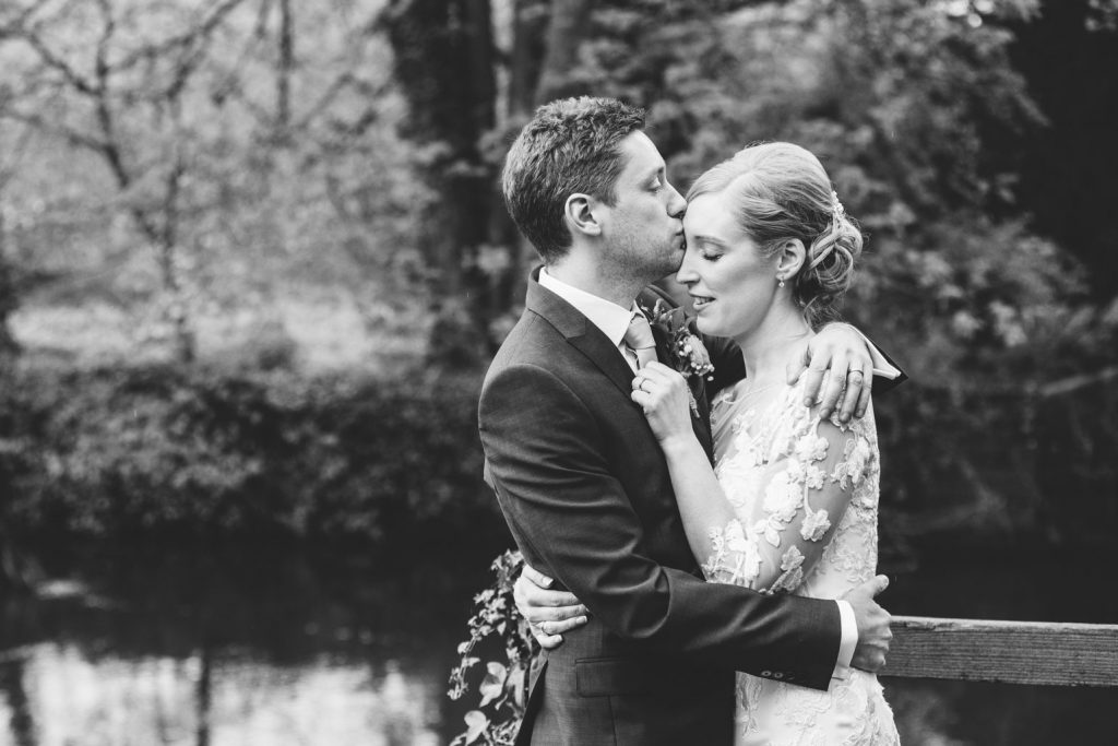 BRide & Groom standing by the riverside at The Saxon Mill, Warwickshire
