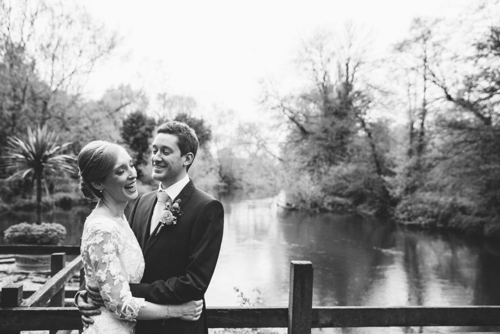 Balck and white image of the bride and groom laughing, standing by the river at their wedding