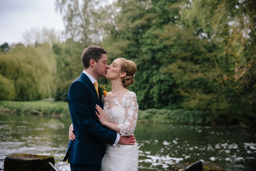 Bride and groom kissing, riverside at The Saxon Mill