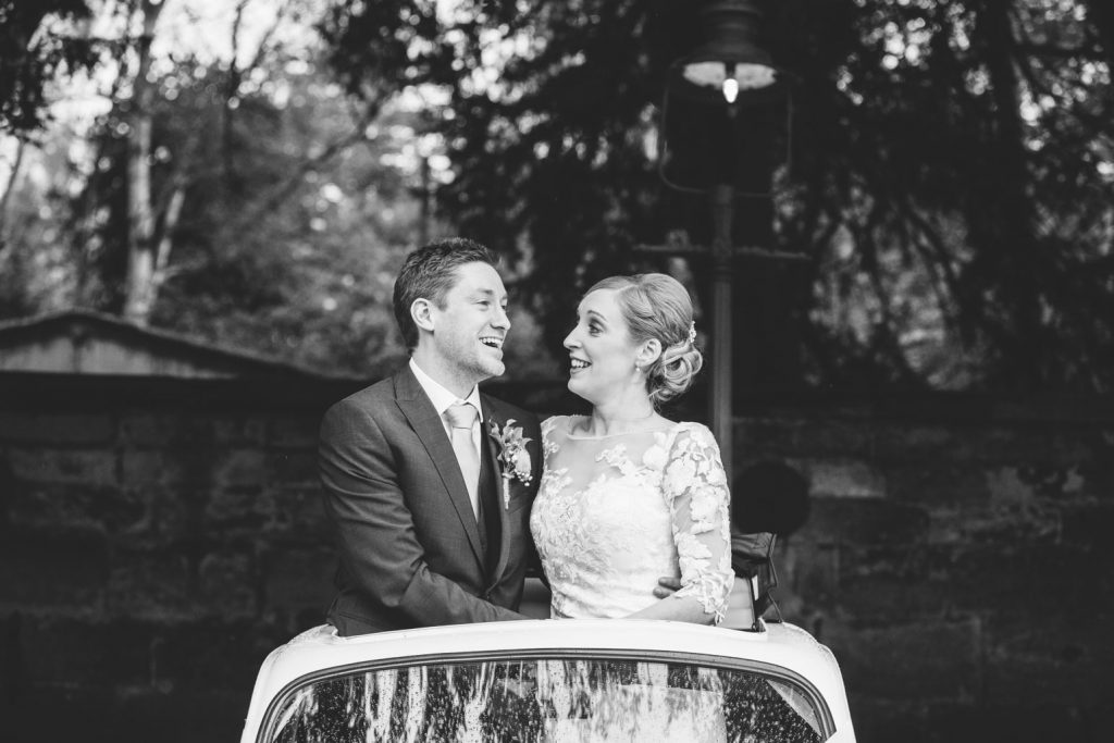 Bride and Groom standing through the sunroof of Fiat 500, wedding car