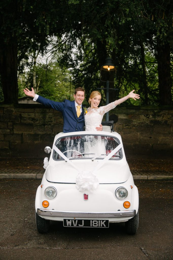 Bride and Groom standing up through roof of Fiat 500 wedding car, Saxon Mill