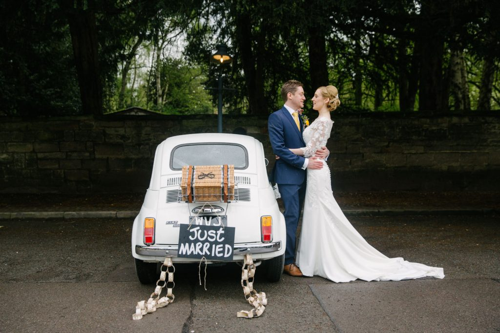 Bride and Groom standing leaning against Fiat 500 wedding car with just married sign, Saxon Mill