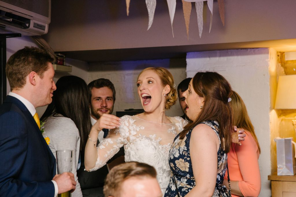 Bride laughing with guest at her wedding reception, Saxon Mill