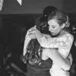 Bride hugging bridesmaid on dance floor at wedding