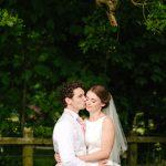 Groom kissing bride under a tree