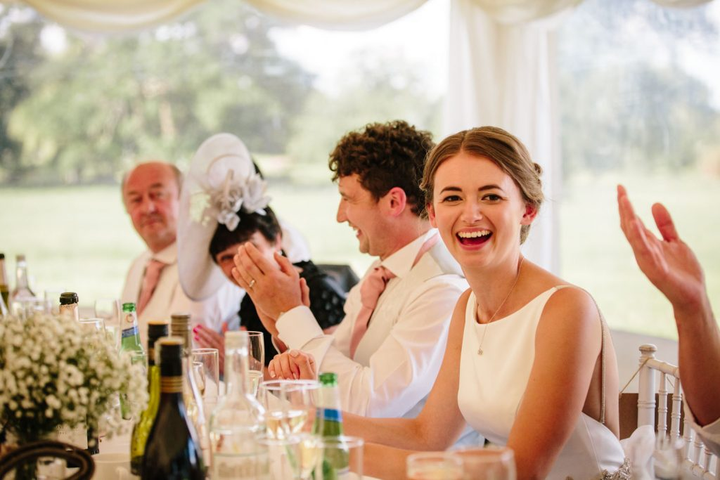 Bride laughing during wedding speech in marquee