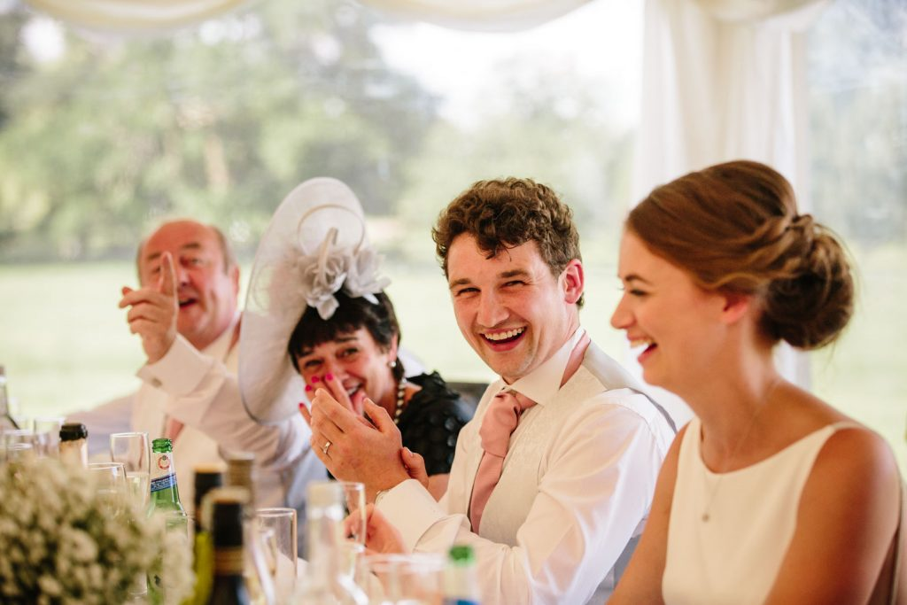 Groom laughing during wedding speech in marquee