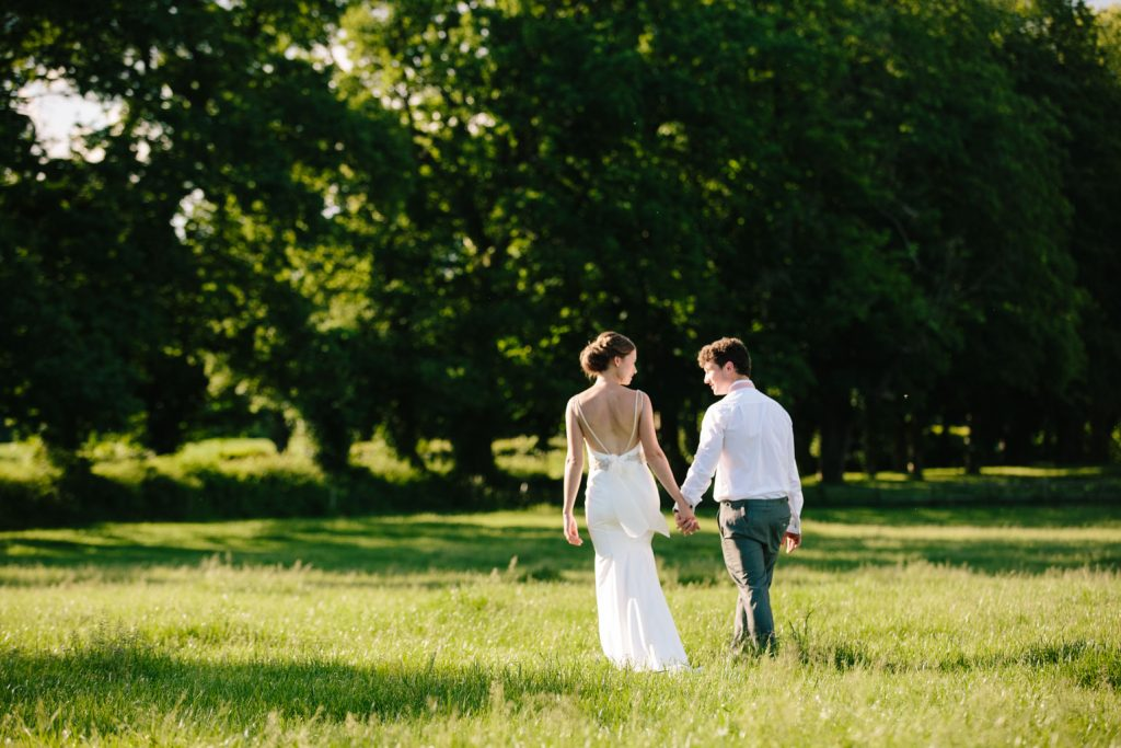 Bride and groom walking hand in hand across a field as the sun goes down