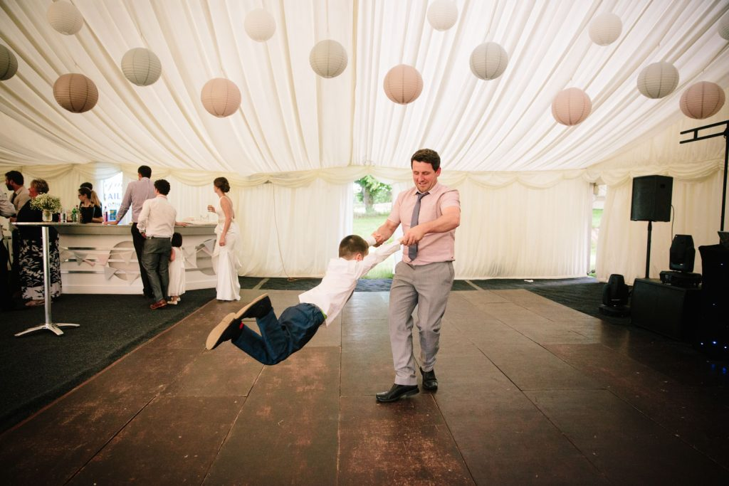 Man swinging child round on the dance floor