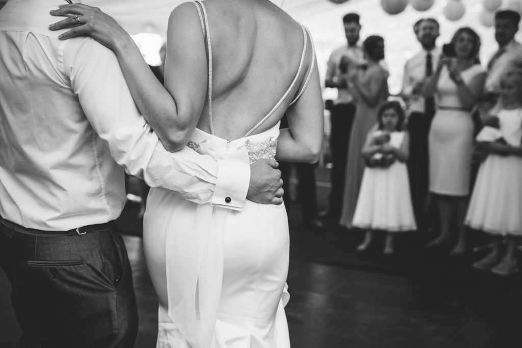 Grooms hand around brides waist on dance floor