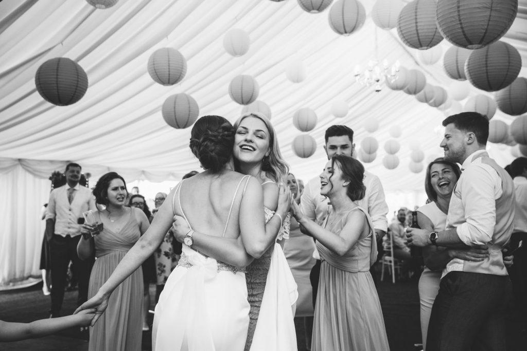 wedding guest hugging bride on dance floor