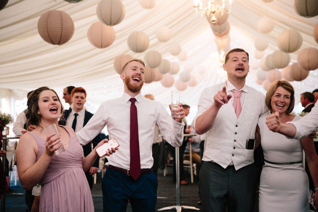 Wedding guests singing on the dance floor
