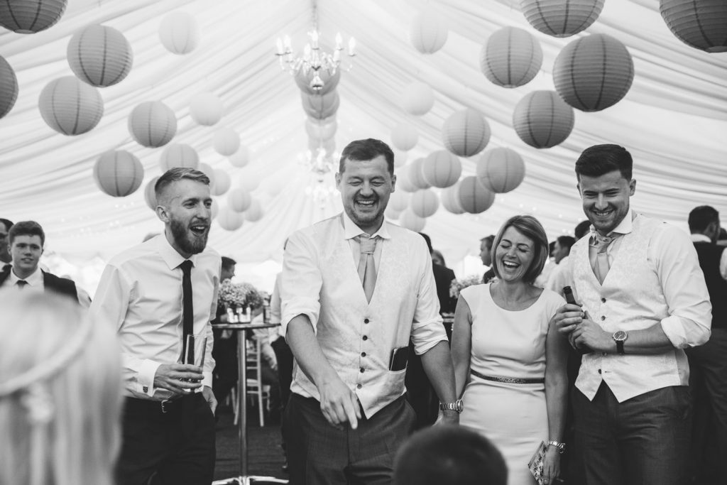 Black and white image of wedding guests laughing on the dance floor
