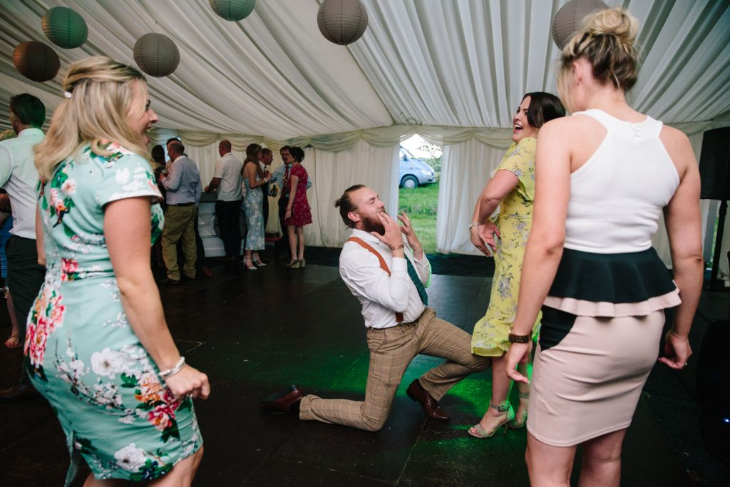 Wedding guests dancing and laughing at marquee wedding