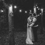 Bride & Groom kissing under fairly lights at Shustoke Farm Barns