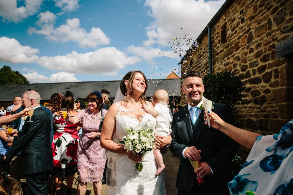 dodford manor wedding, confetti being thrown over Bride & Groom