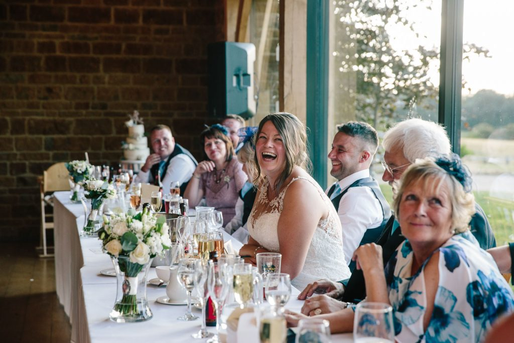 The bride laughing on top table, during speeches at wedding breakfast, dodford manor