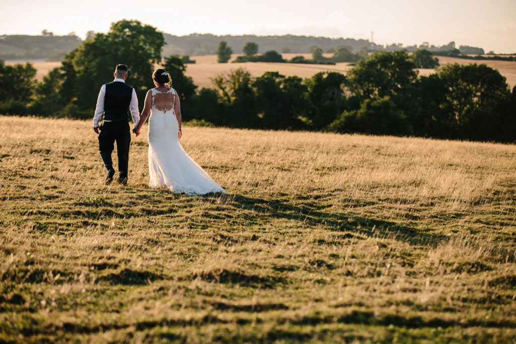 Bride and Groom walking in the sunset at Dodford Manor wedding