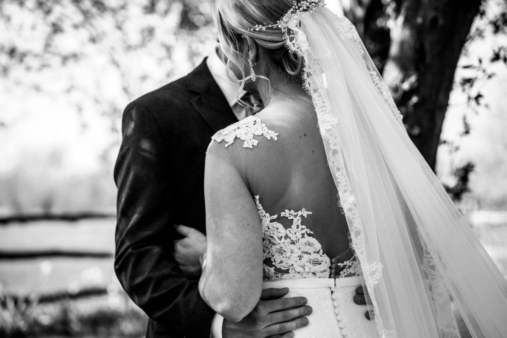 black and white image of bride and groom hugging, with lace detail on back of dress