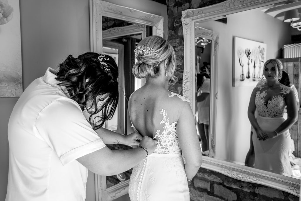 Bridesmaid doing up bride's wedding dress, blackwell grange