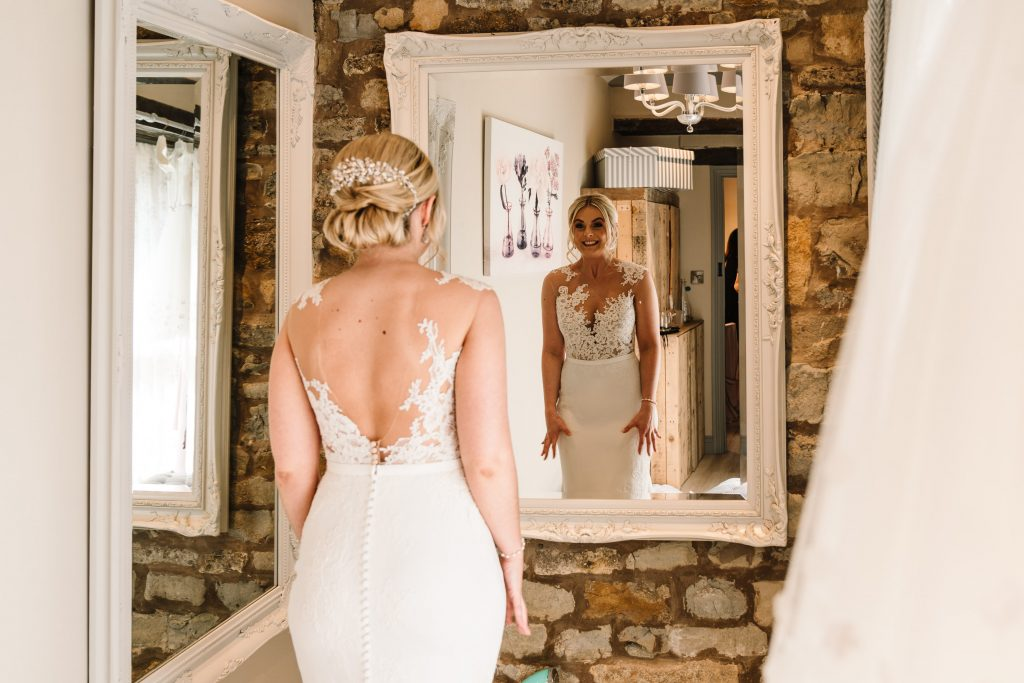 Bride looking at herself in mirror in wedding dress at blackwell grange