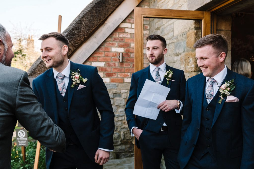 Groom and groomsmen greeting guests arriving for wedding