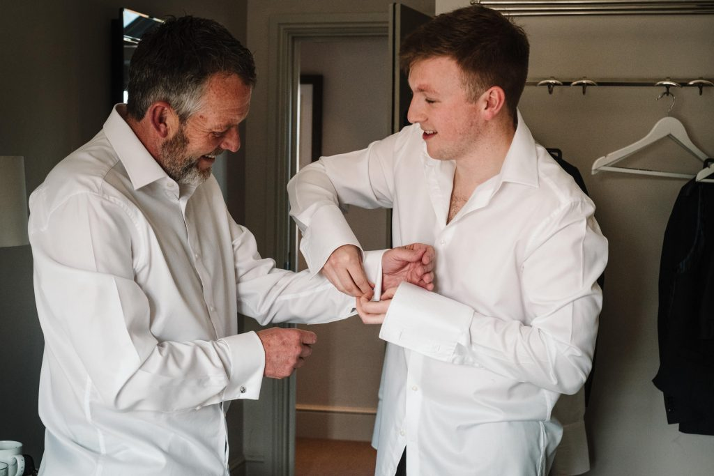 Groom doing up his Dad's cufflinks