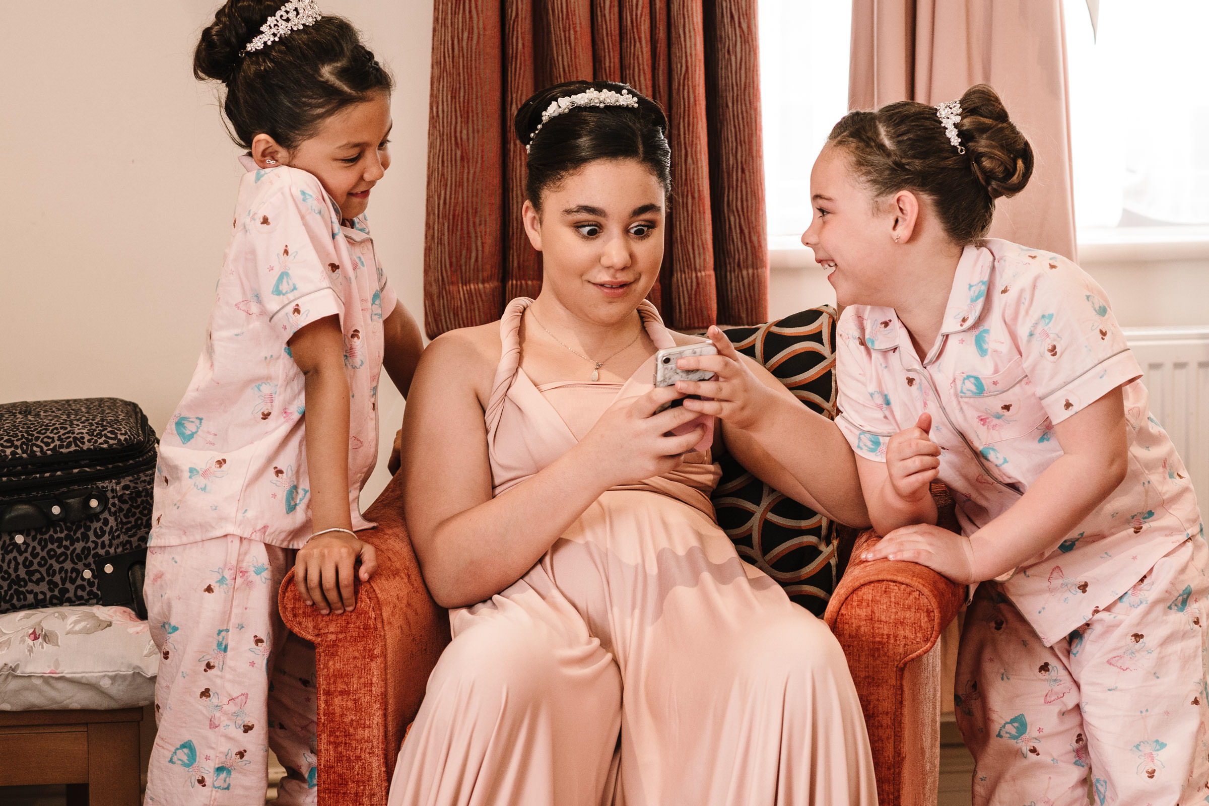 Bridesmaid and flower girls laughing at picture on phone