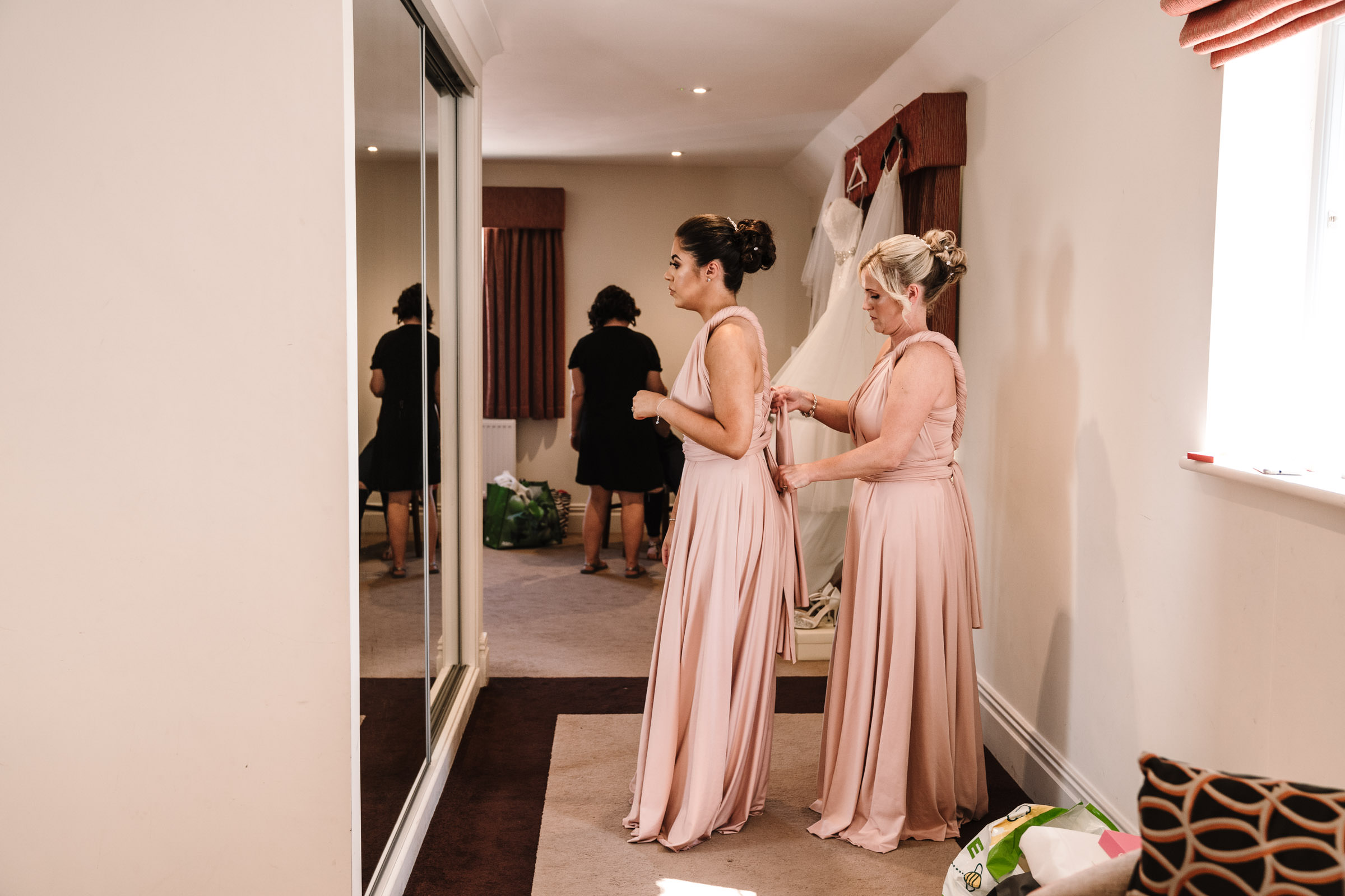 Bridesmaids helping each other put their dresses on, Nailcote hall wedding