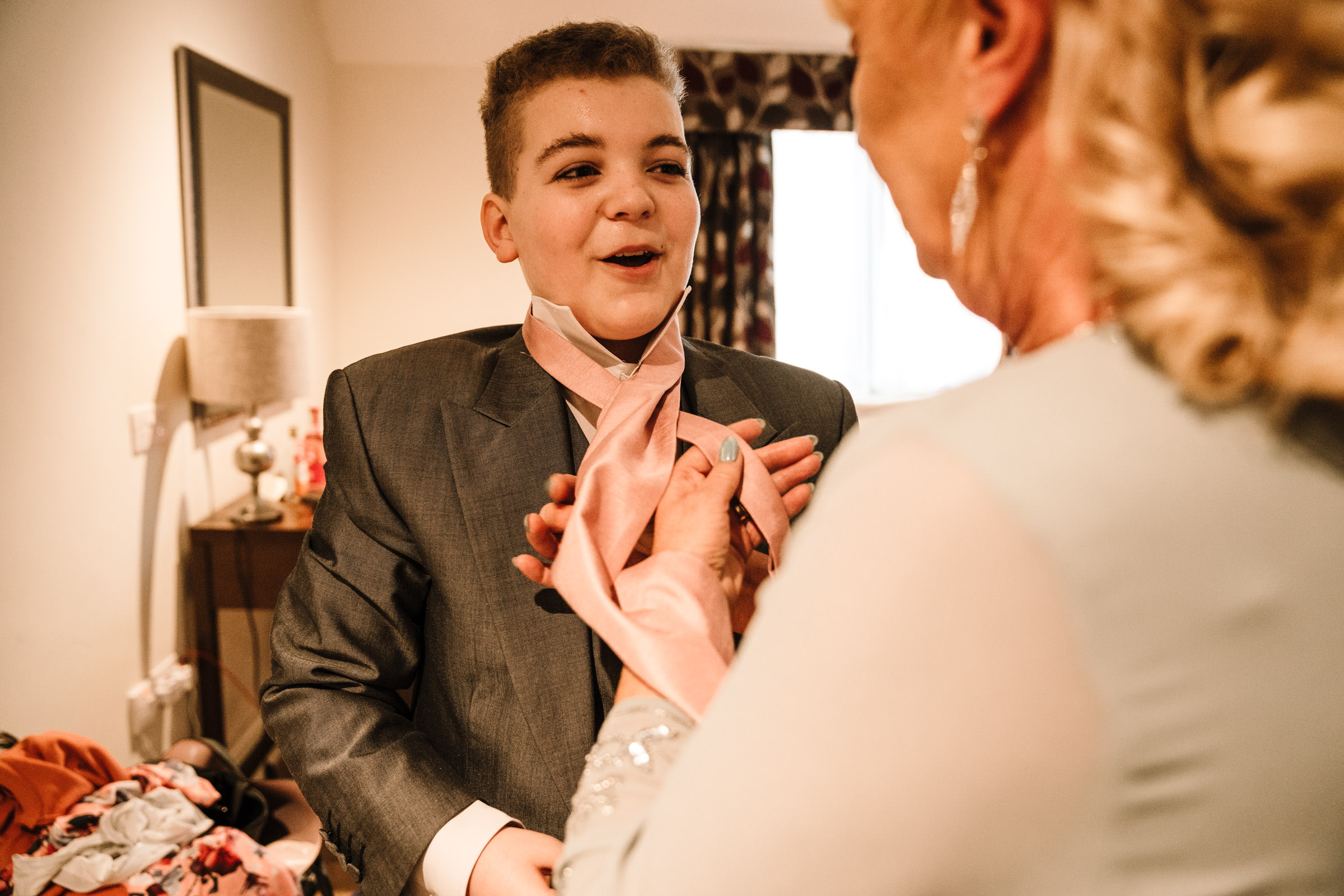 Mother of groom doing tie up for page boy