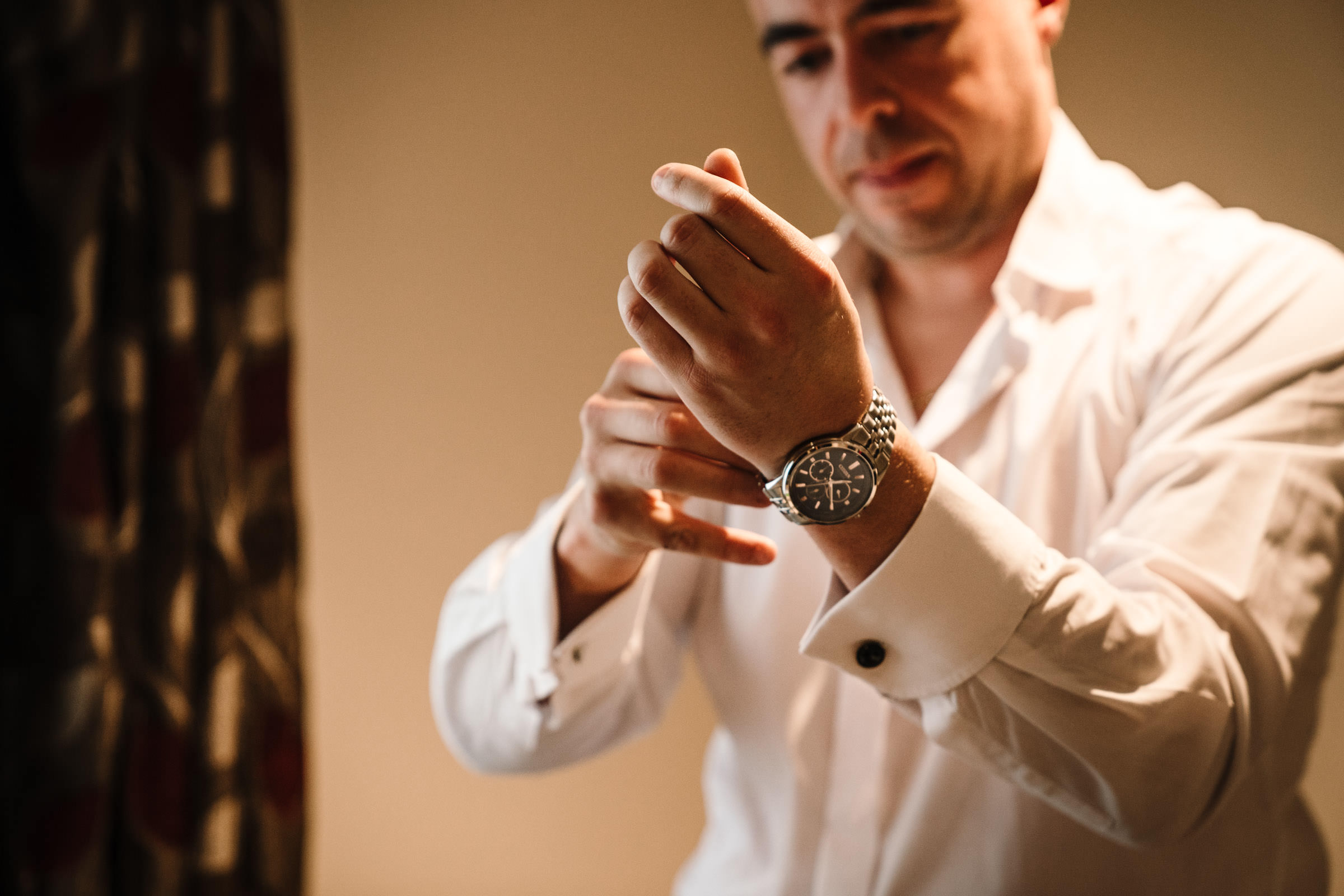 Groom putting on his new watch from his Bride