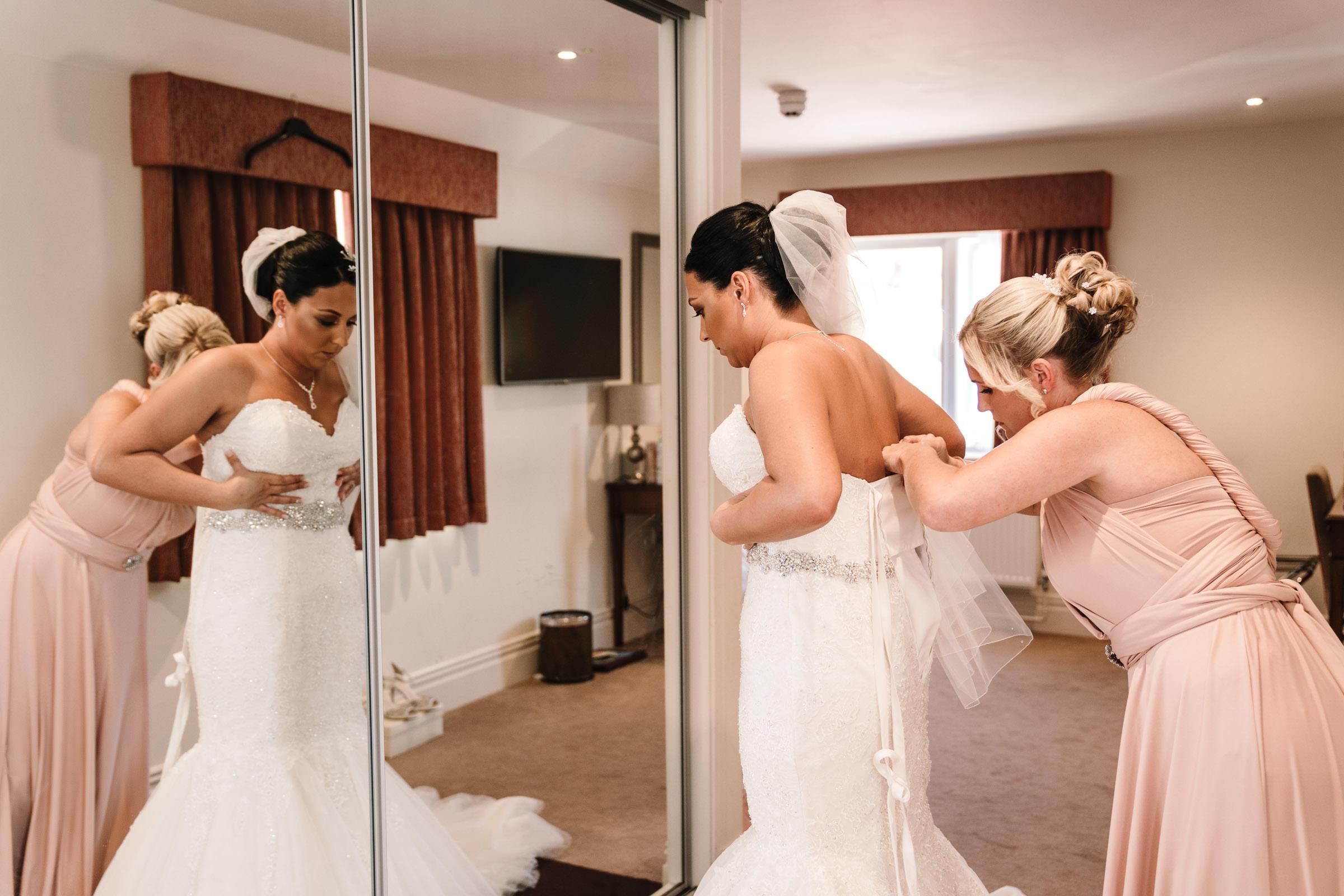 Bridesmaid doing up brides dress before nailcote wedding