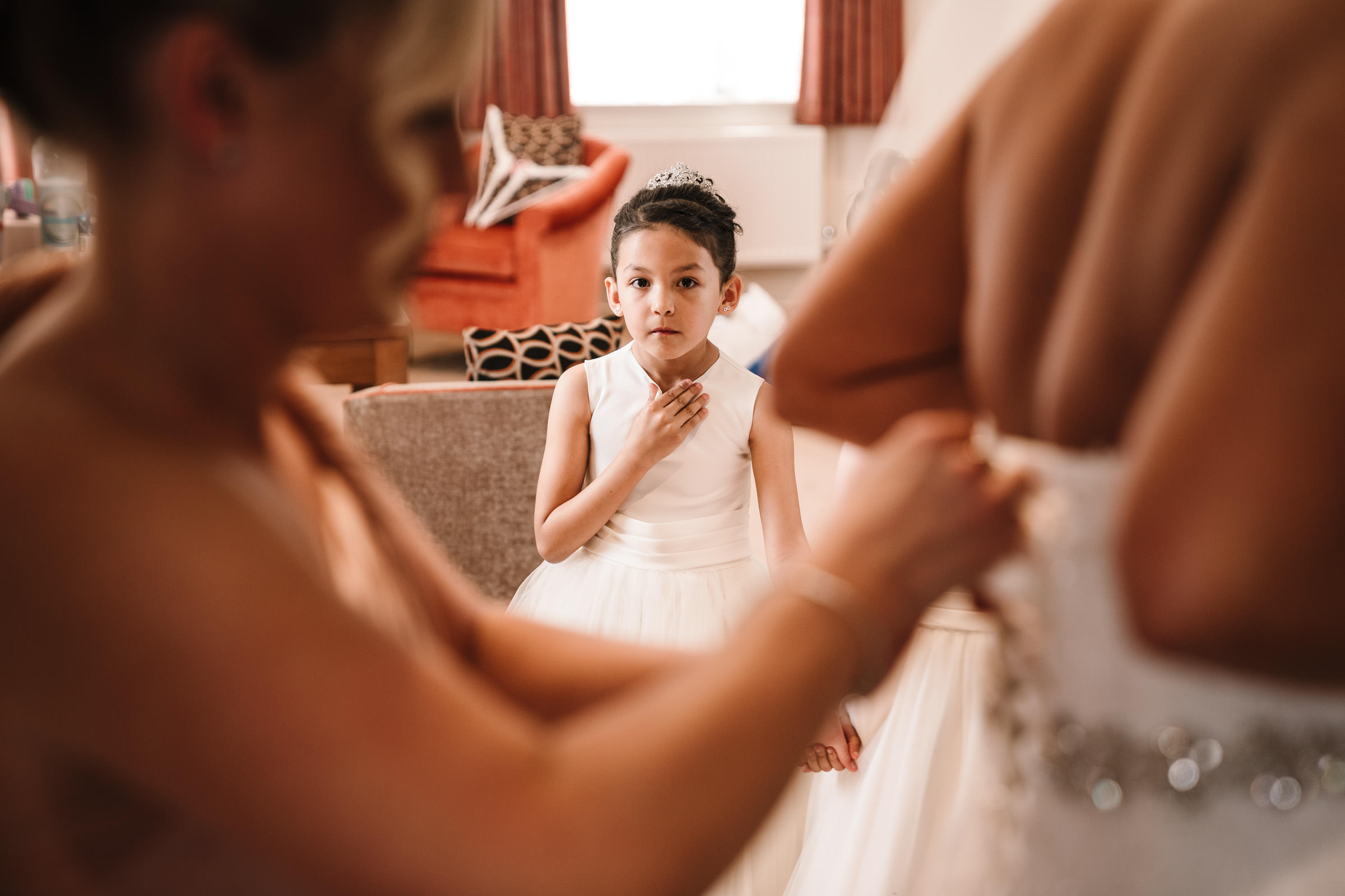 flower girl watching bride get dressed for wedding at nailcote hall