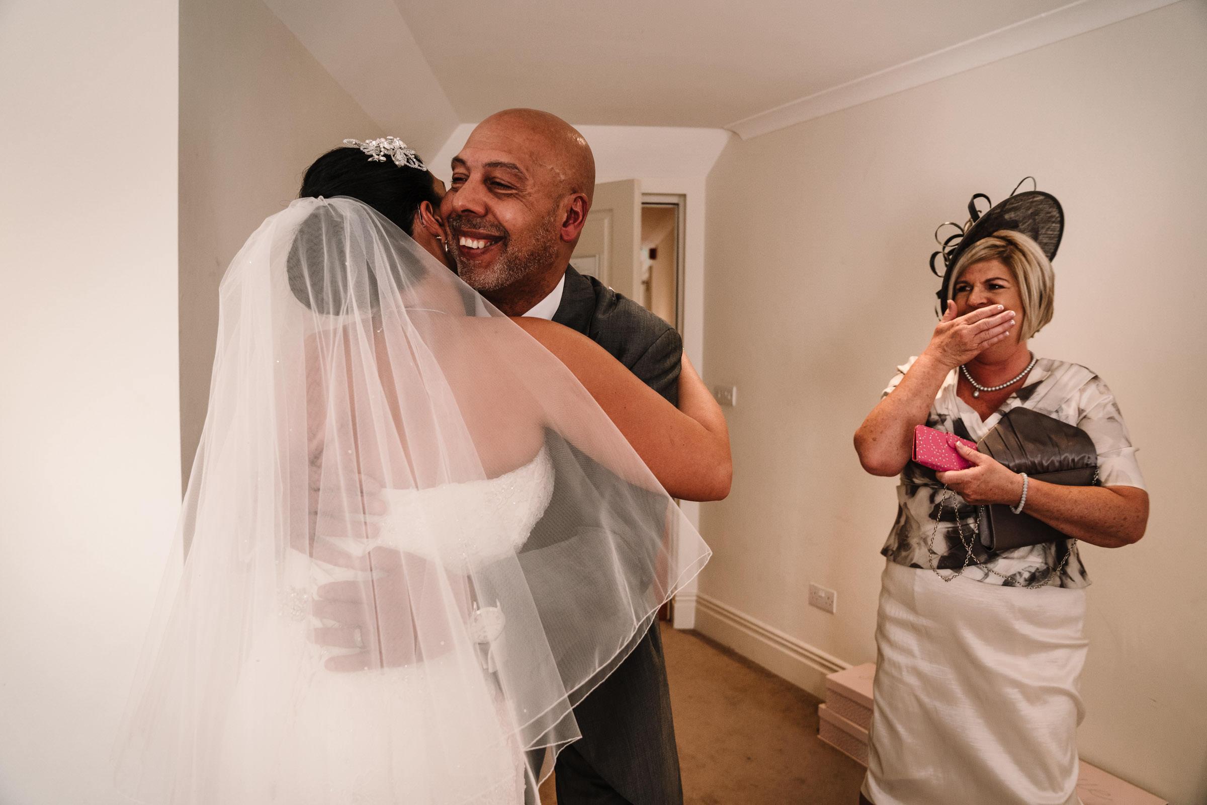 Dad hugging bride, mum getting emotional