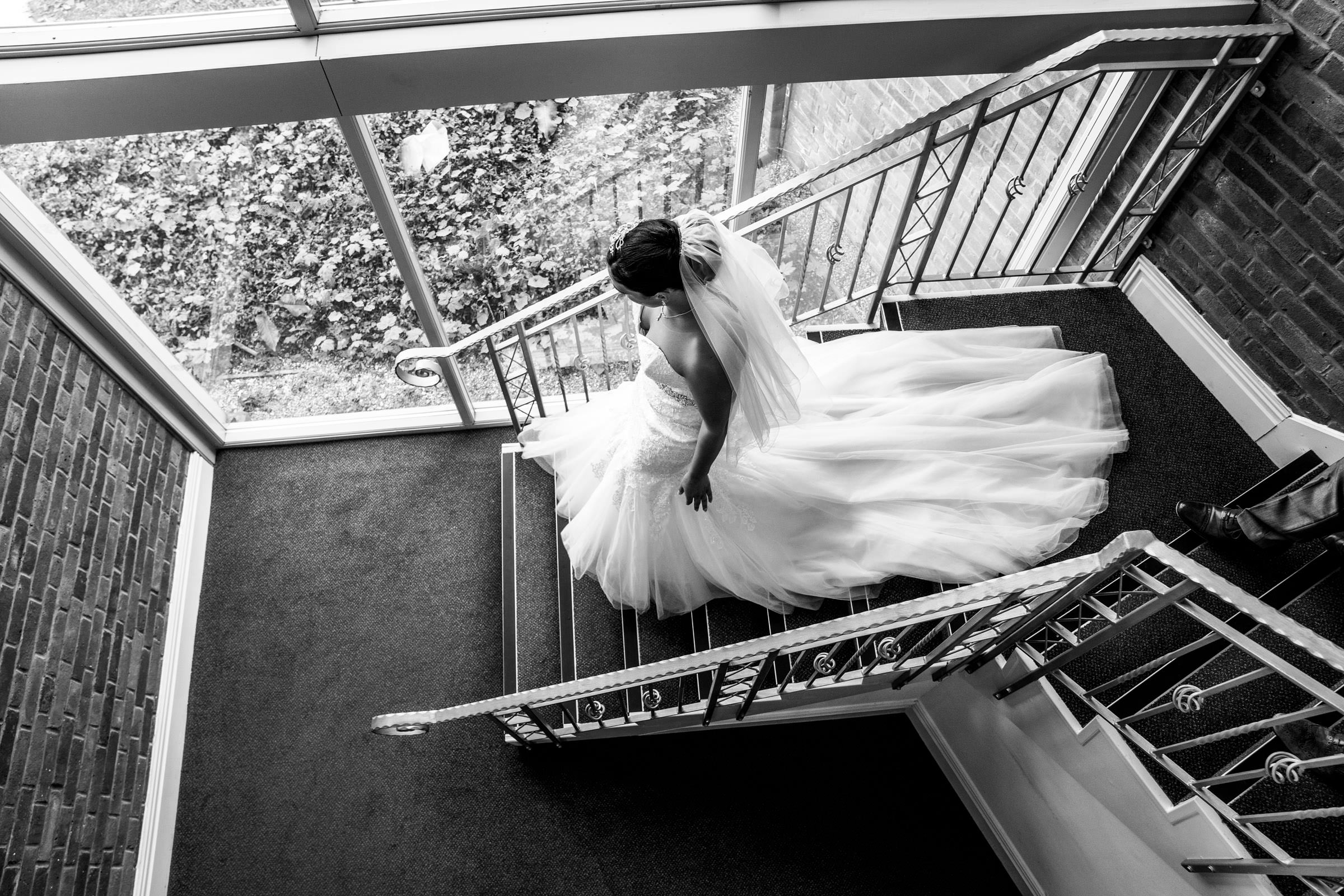 Bride walking down the stairs ready to go to her wedding at Nailcote hall