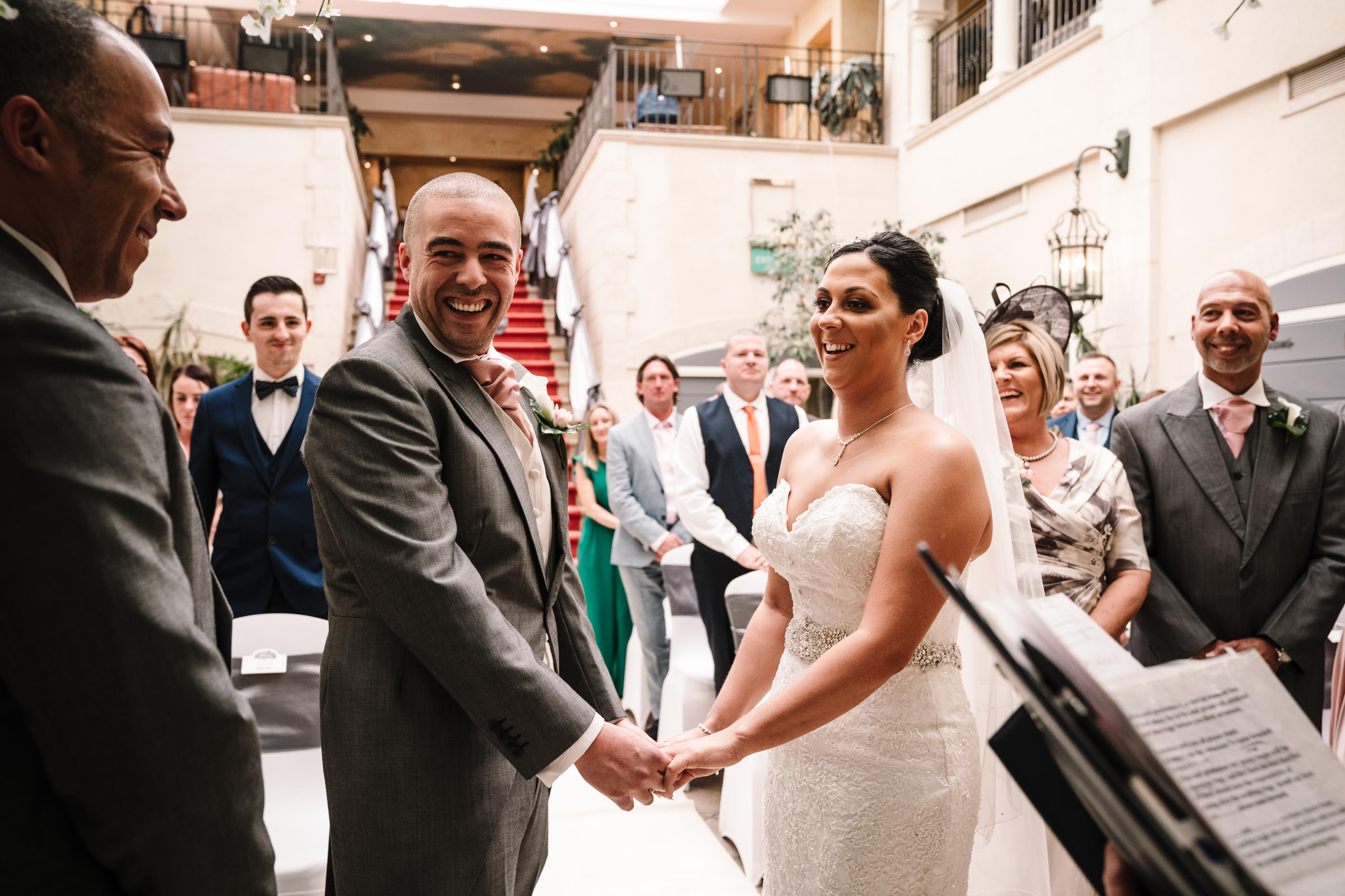 Brid mand groom laughing during nailcote hall wedding ceremony