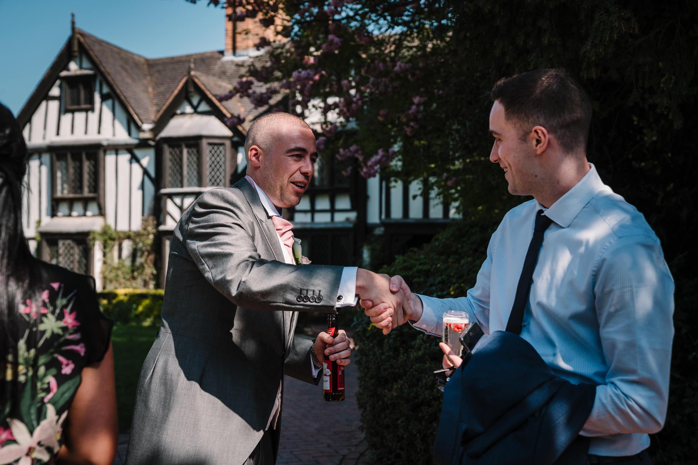 Groom greeting guests at nailcote hall wedding