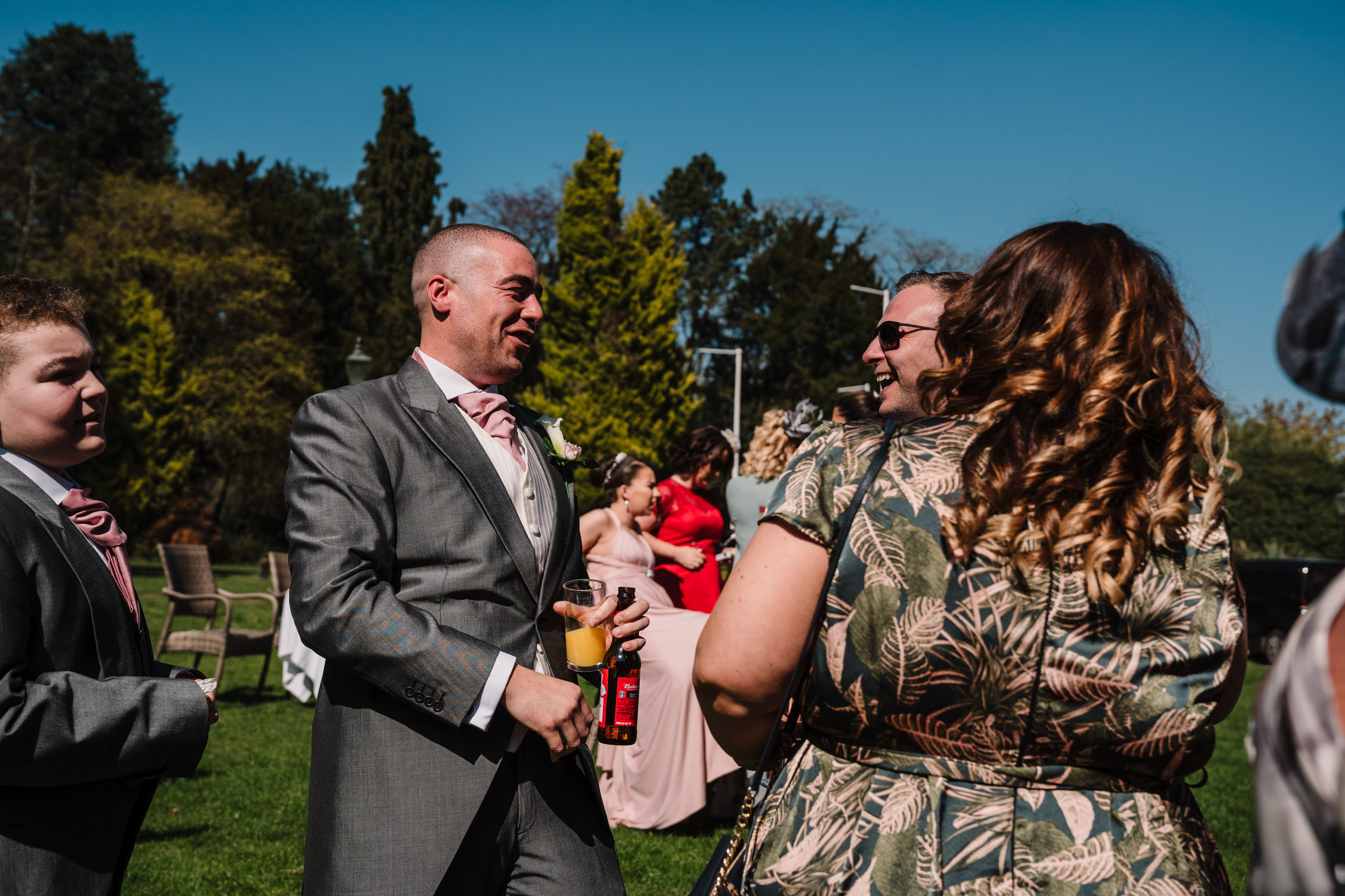 Groom laughing with guests at nailcote hall wedding