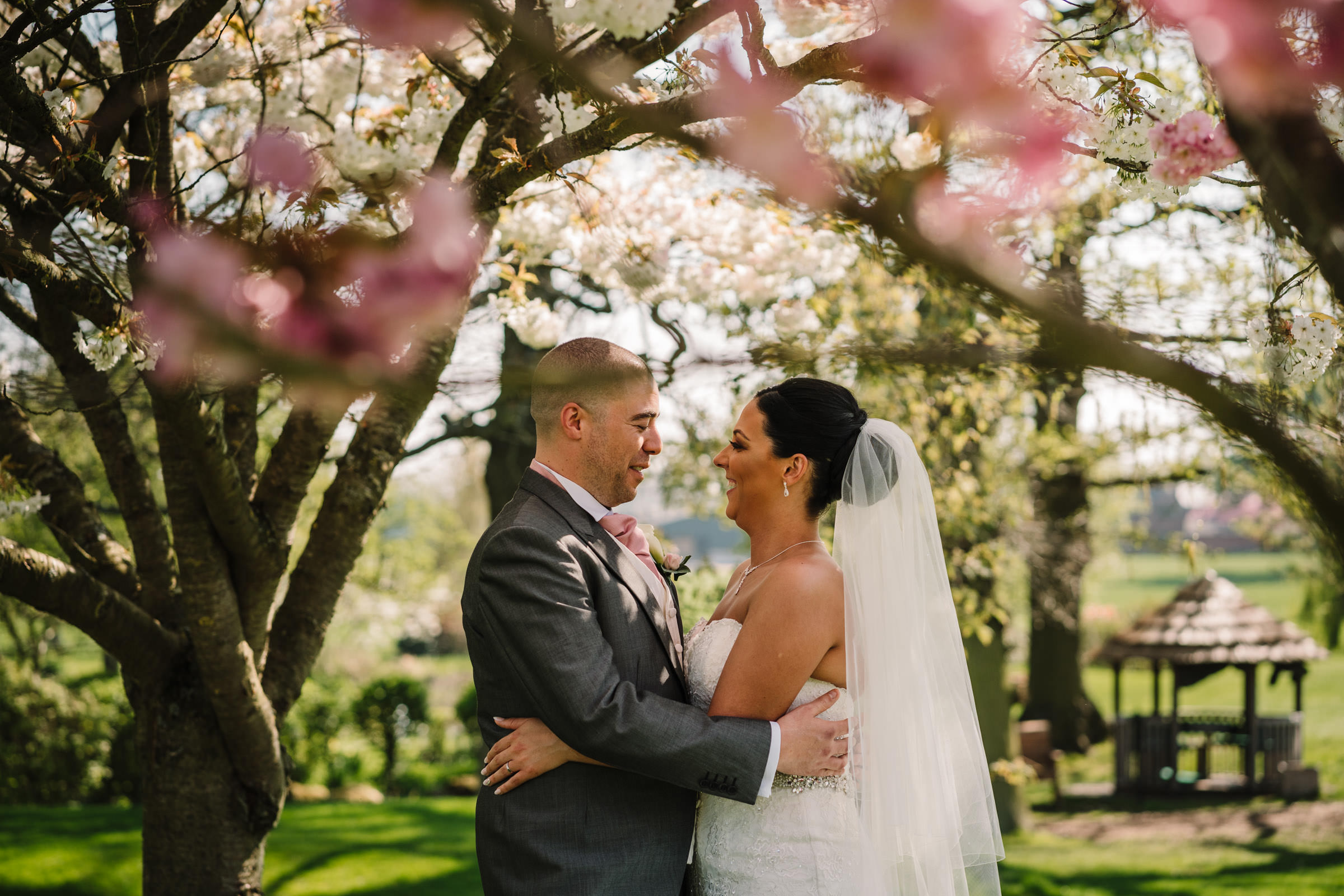 bride and groom hugging under blossom tree, Nailcote Hall