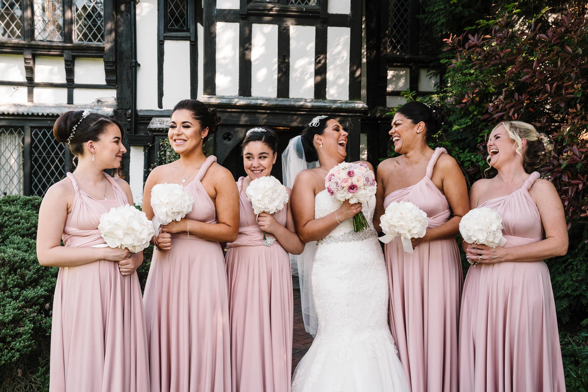 Bride laughing with bridesmaids at nailcote hall wedding