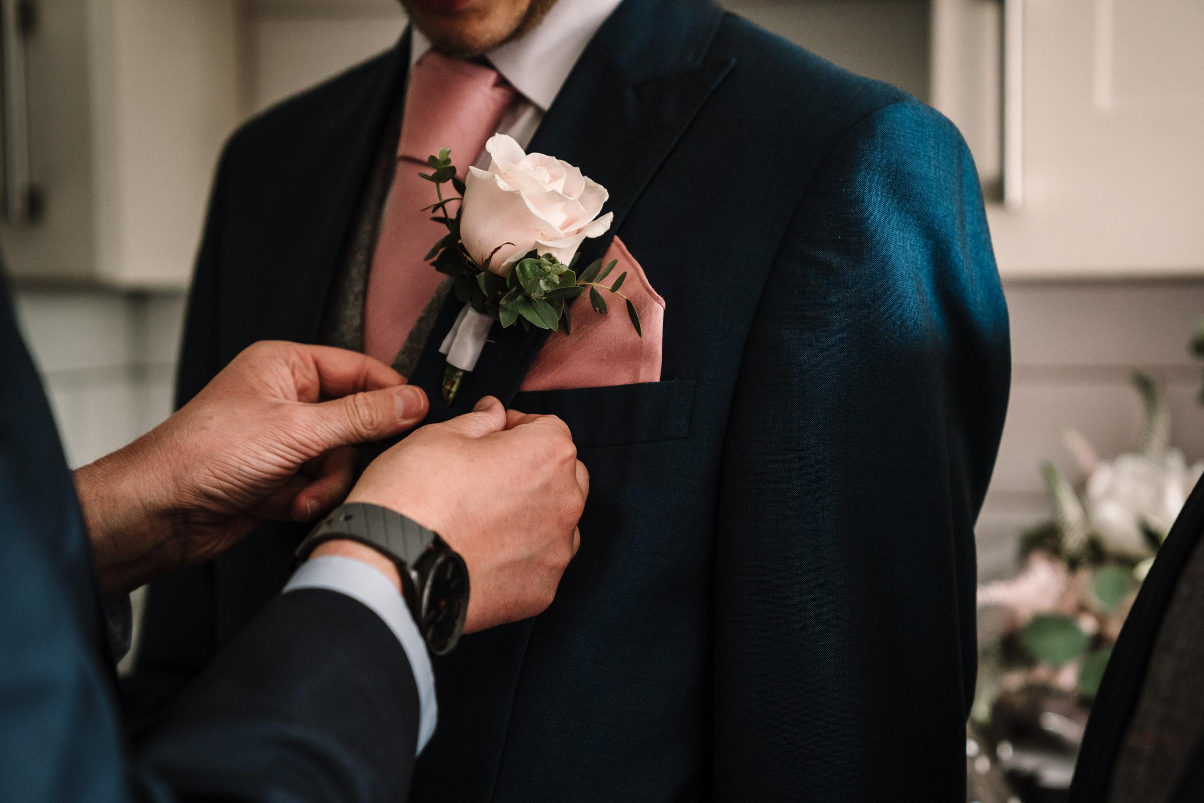 groomsmen attaching buttonhole