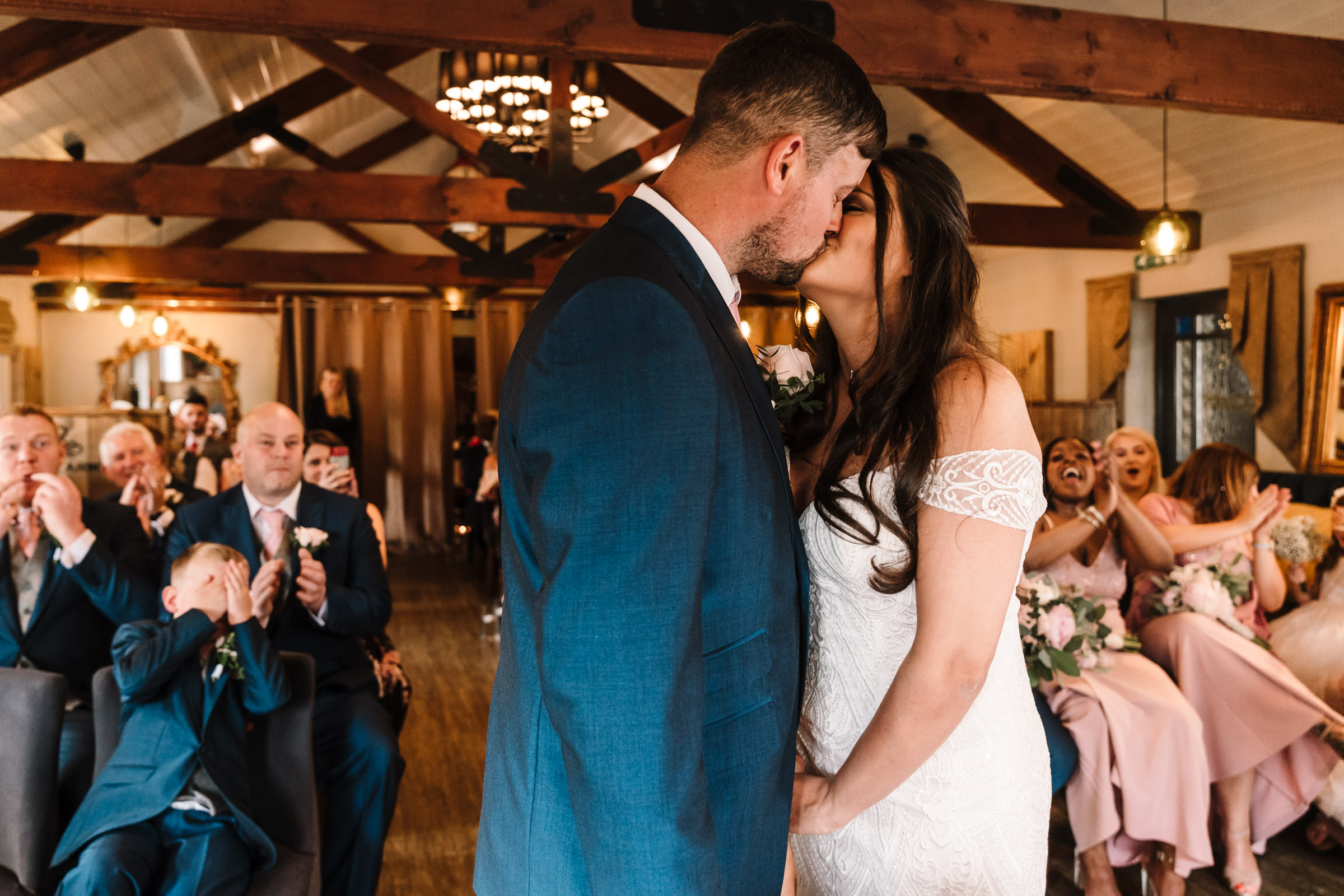 Bride and groom first kiss during wedding ceremony, royal arms hotel wedding
