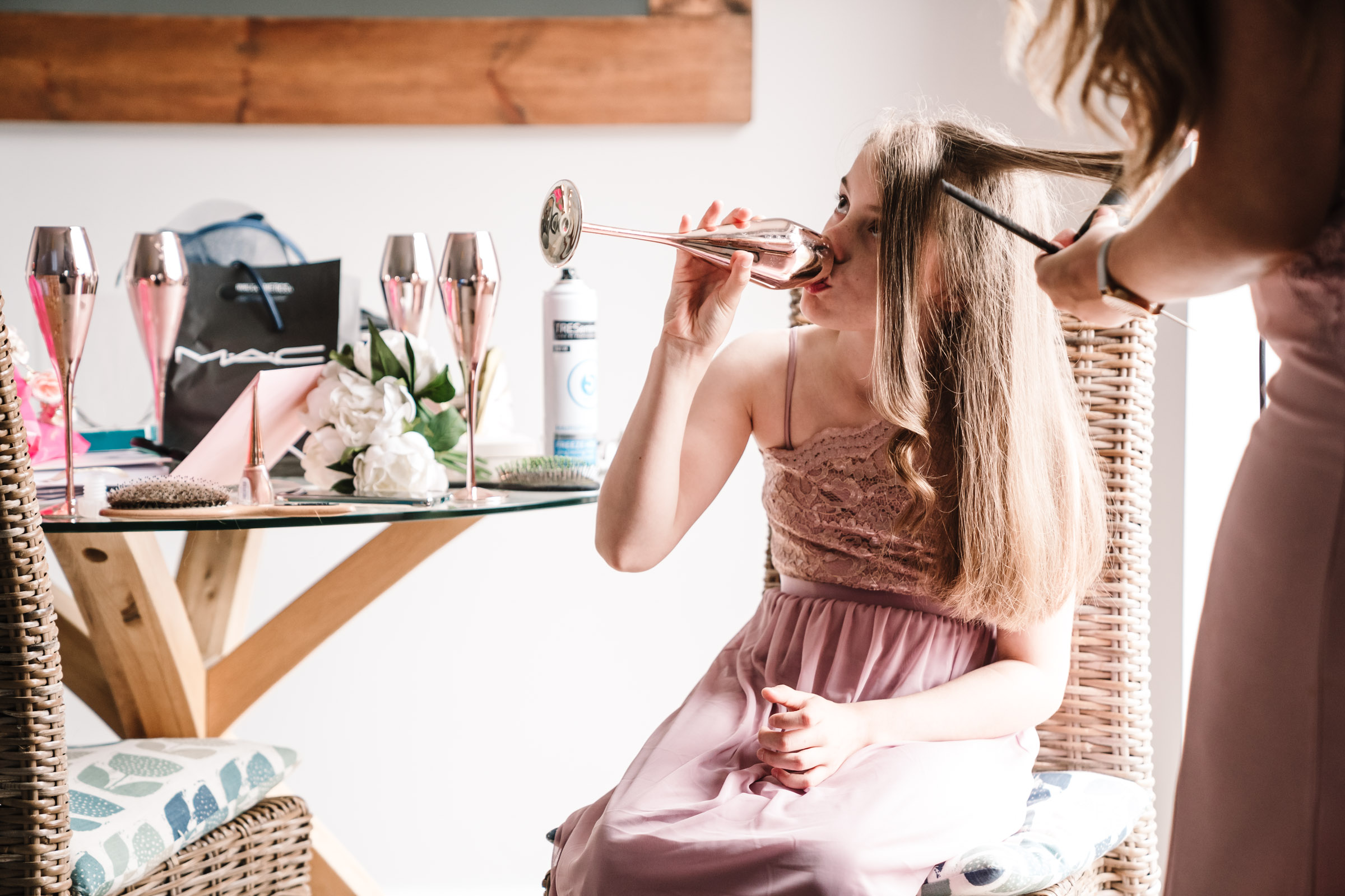 young bridesmaid swigging a drink from a champagne flute