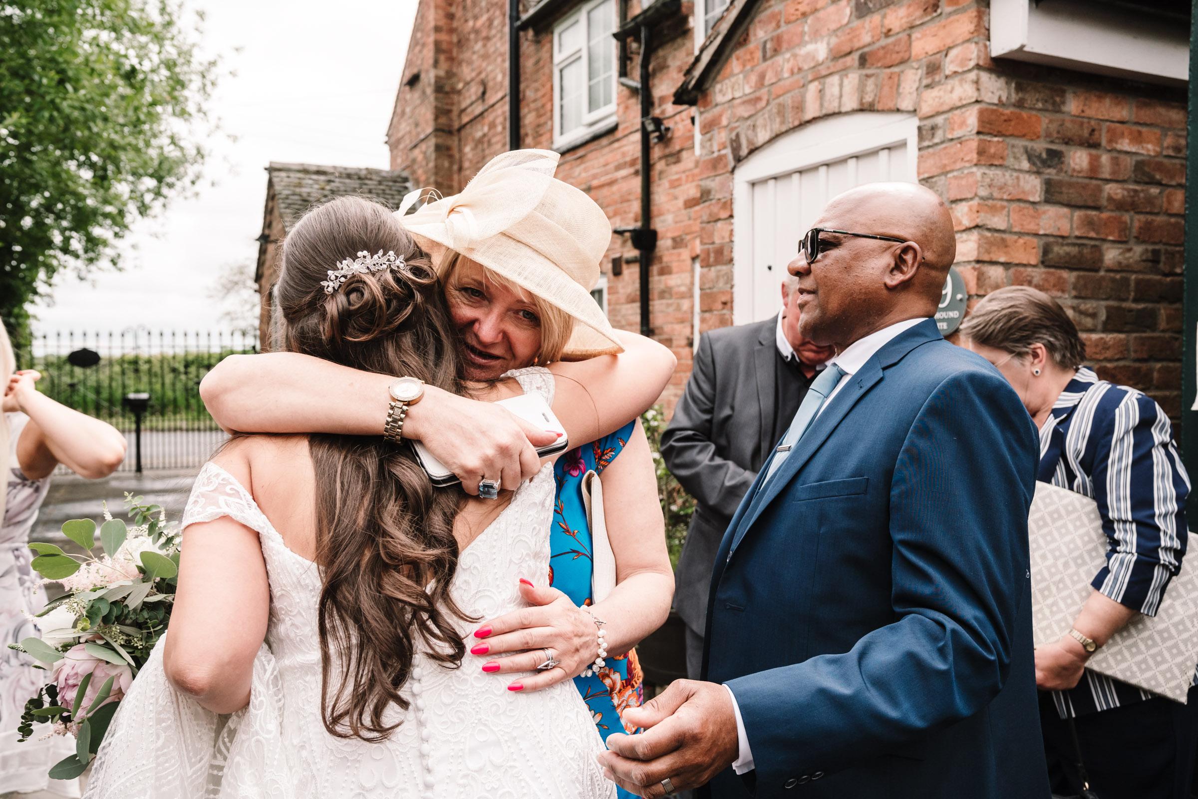 Wedding guests hugging bride, leicester wedding