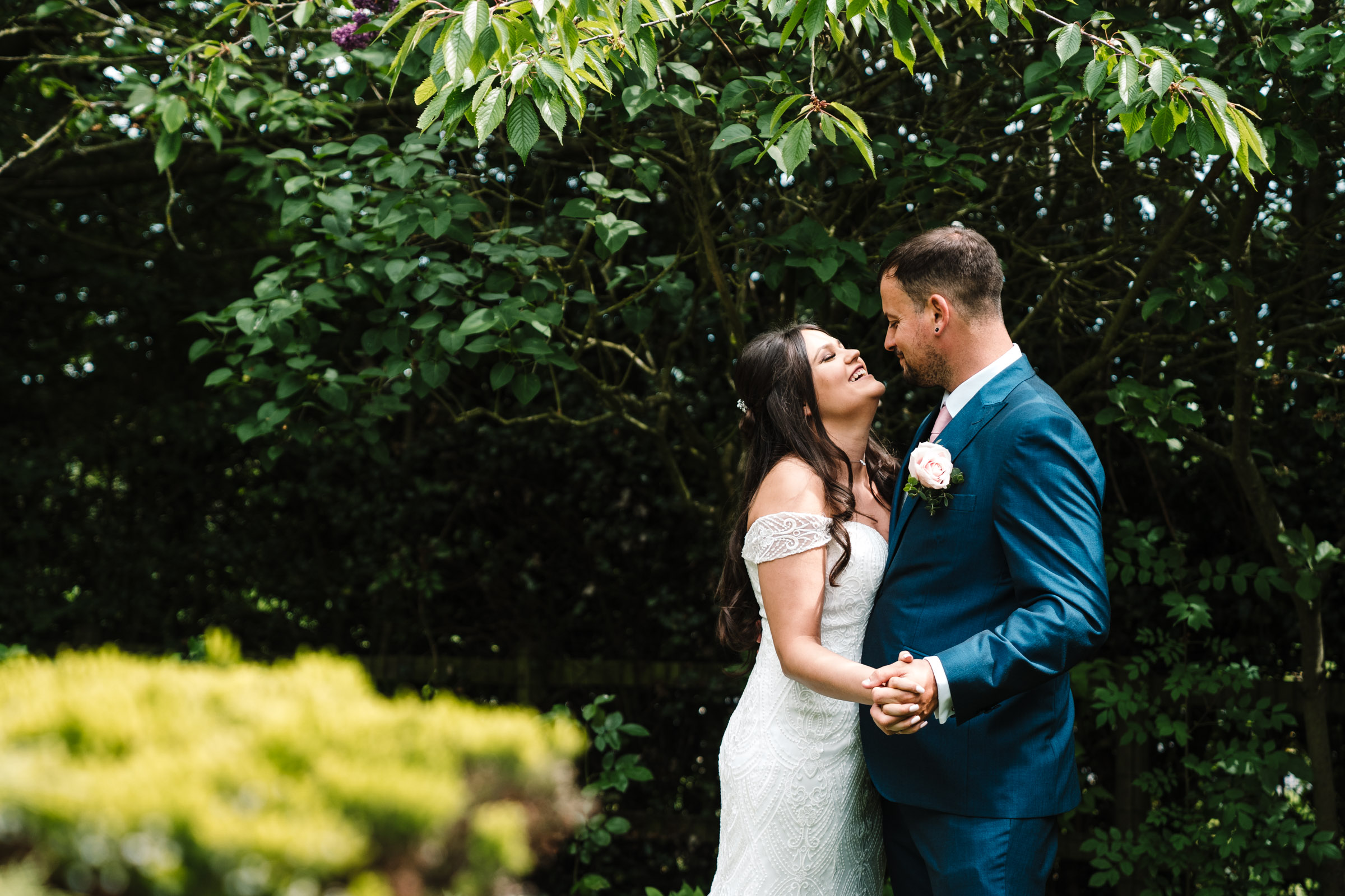 Bride and groom laughing , arm in arm in royal arms hotel garden